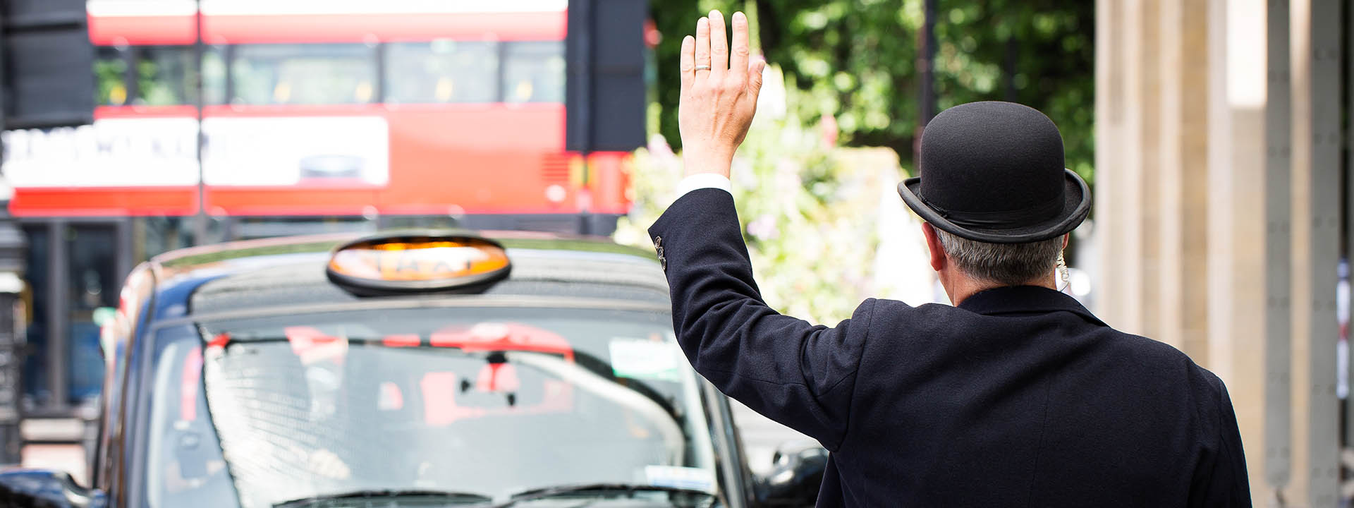 Hotel doorman hailing a black taxi outside The Berkeley