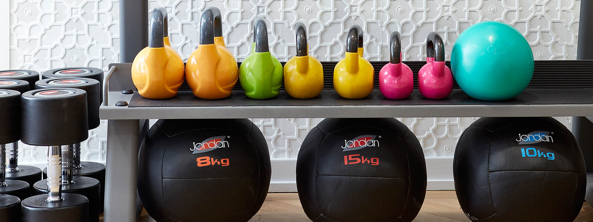 A row of kettle bells and medicine balls