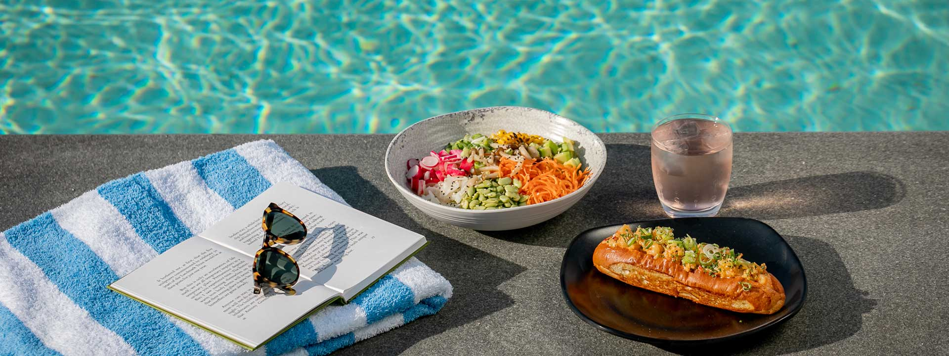 A hotdog, a salad and a chilled fruity drink at the edge of the pool