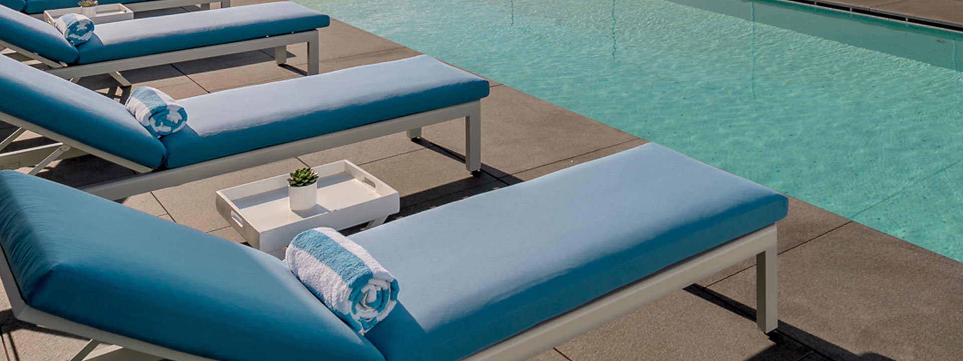 Four blue sunbeds facing the pool water on the rooftop of The Berkeley
