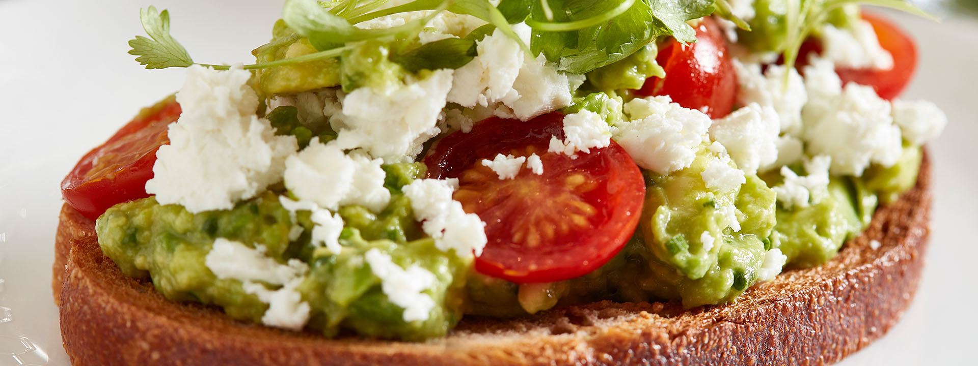 Avocado toast with tomatoes, rocket and feta cheese for breakfast at The Berkeley