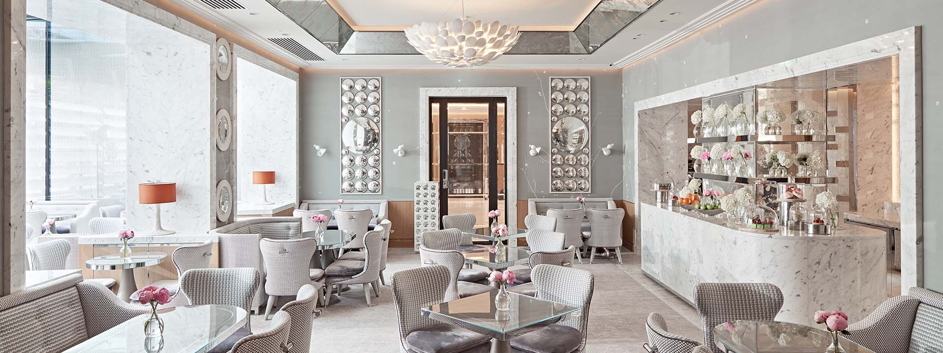 Collins Room restaurant light grey interior, with velvet grey seats, glass tables and silver wall decorations at The Berkeley