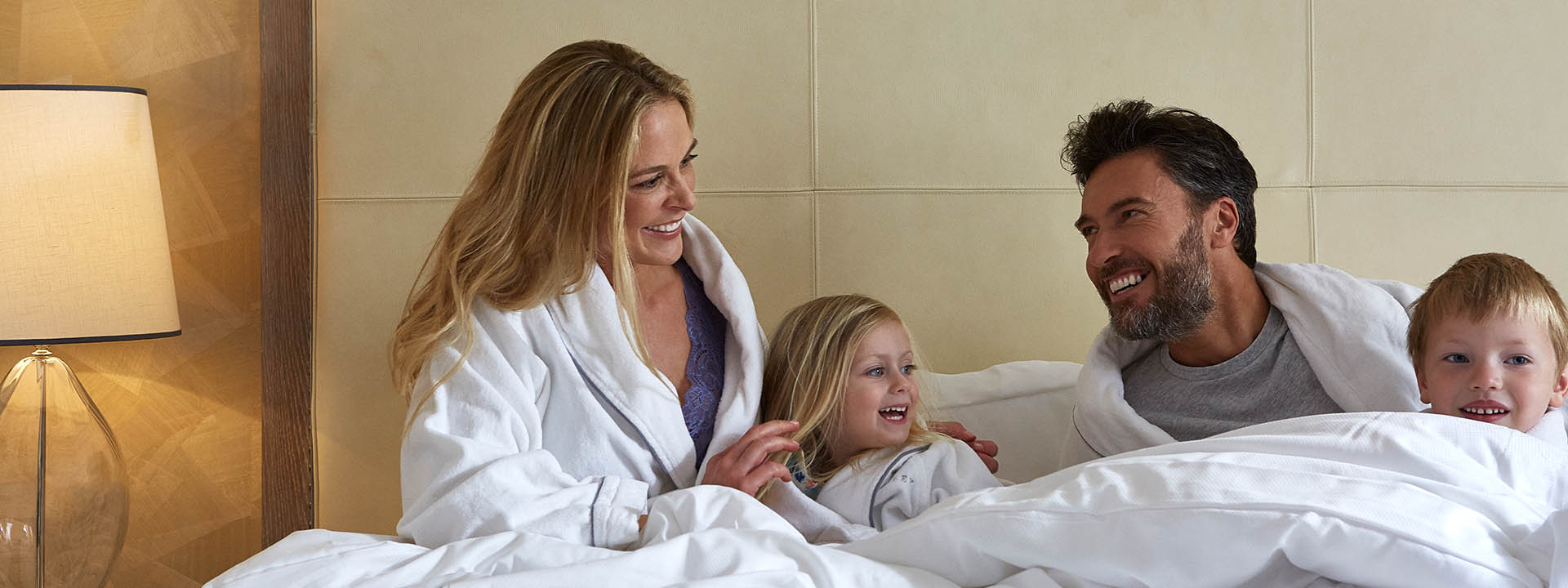 Happy family smiling in bed